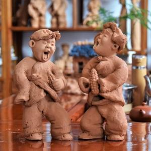 泥塑作品:抱玉米的娃娃